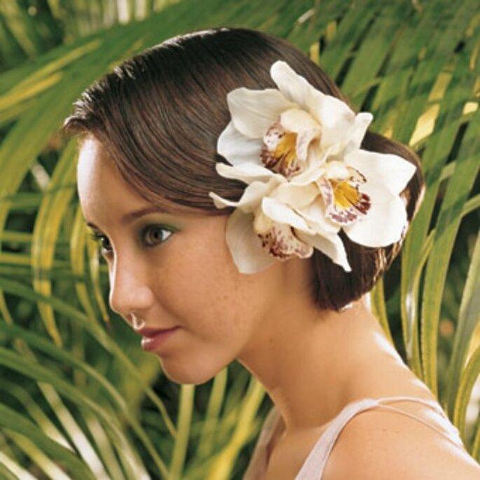 Soluzione esotica per questa acconciatura con orchidea a lato. Foto www.100matrimoni.it