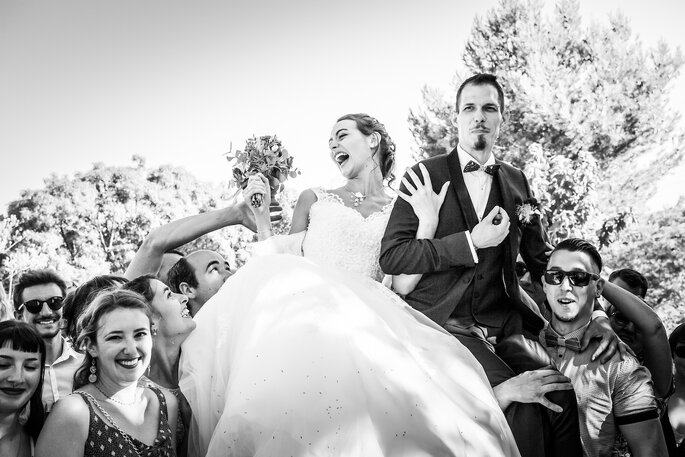 Un couple de mariés porté par leurs invités dans une ambiance festive