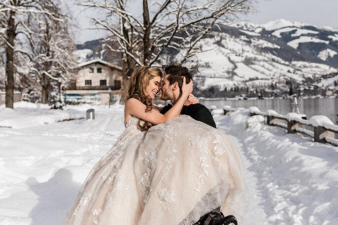 Hochzeitsfoto.Bräutigam trägt Braut auf Armen in Schneekulisse