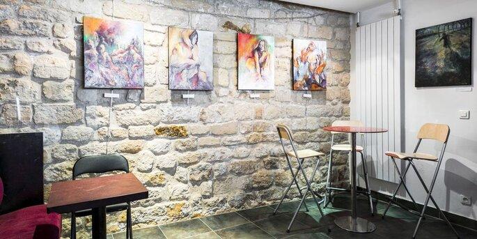 Tableaux accrochés sur un mur de pierre dans la salle du Macareux.