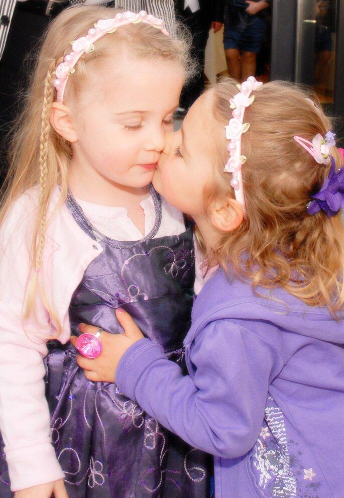 Zwei Blumenmädchen geben sich bei einer Hochzeit ein Küsschen.