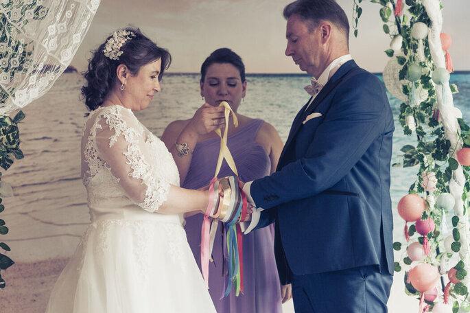 Anaïs et ses mariés en pleine cérémonie laïque tenant des tubans sous une arche décorée avec des lampions et l'océan en toile de fond