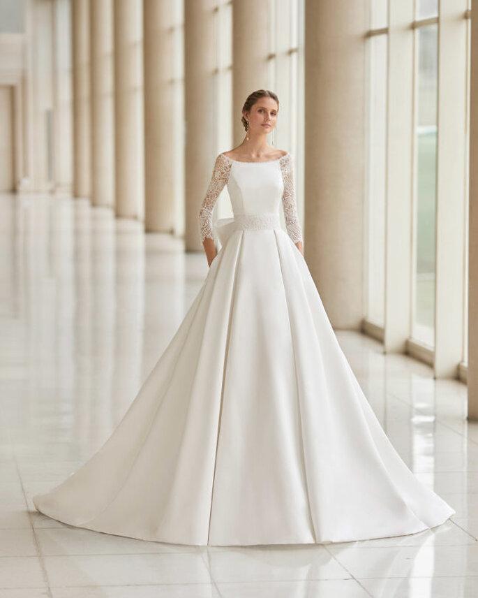 Aire Barcelona vestido de novia en corte princesa con escote barco, mangas francesas, espalda con ilusión, amplia falda con bolsillos y decorada con un lazo gigantesco.