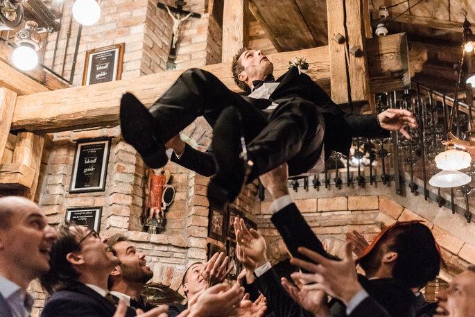 Hochzeitsfeier.Bräutigam hat Spaß mit Gästen