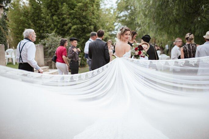 Souffles des Fées - une mariée montrant sa longue traîne avec tous les invités du mariage pour spectateurs