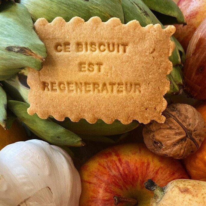 Un sablé au beurre avec un message au milieu d'une pomme, d'une noix, d'une gousse d'ail et d'un artichaut