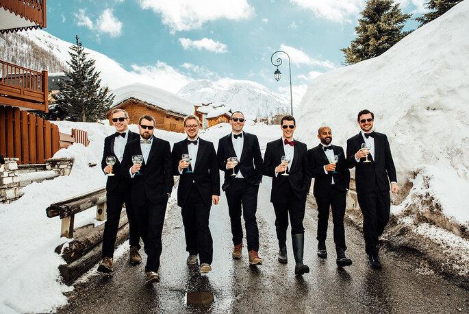 Un mariés et ses amis en costard en train de marcher au milieu de paysages enneigés à la montagne