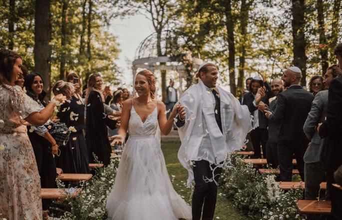 Les mariés sous les ovations de leurs invités à la fin de leur cérémonie en extérieur