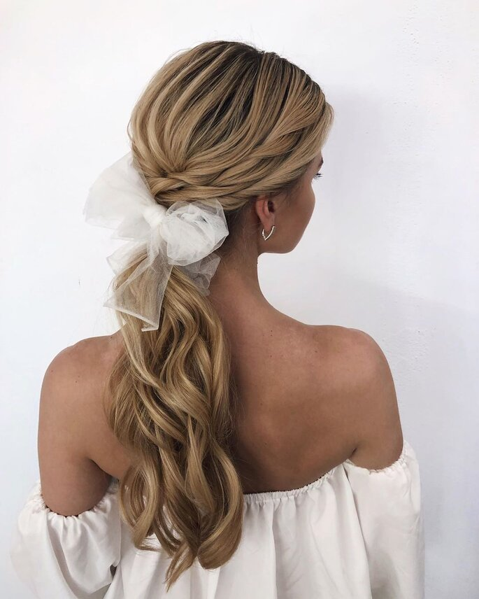Peinado para dama de honor con cola de caballo decorada con lazo de tul