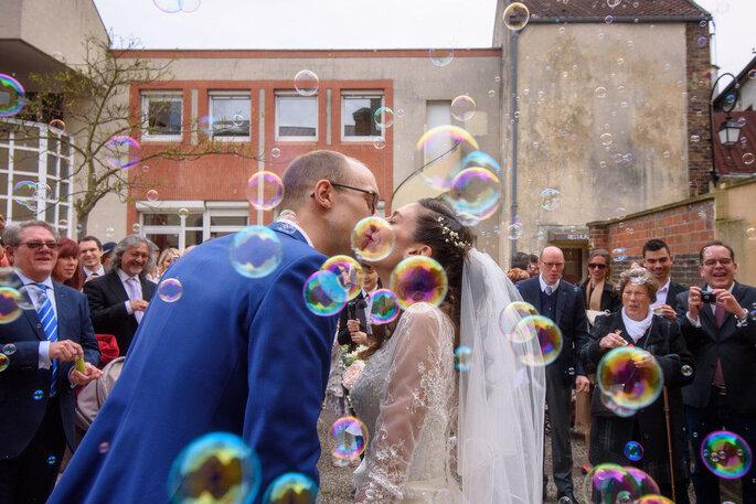 Un couple photographié en train de s'embrasser au milieu de bulles de savon devant leurs invités