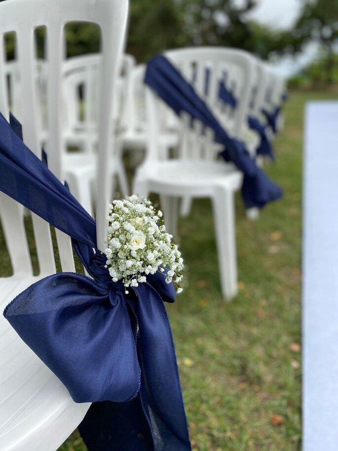 Ruban en soie bleu agrémenté de fleurs pour décorer une des chaises de la cérémonie laïque.