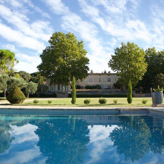 Une piscine avec un parc arboré et une belle demeure en toile de fond