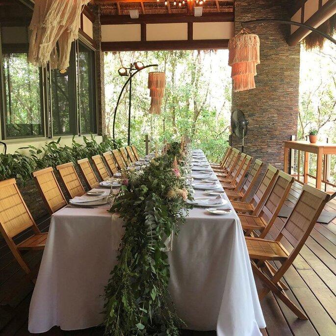 Decoración para mesa con camino de flores y follaje natural, mesa larga y toque espiritual