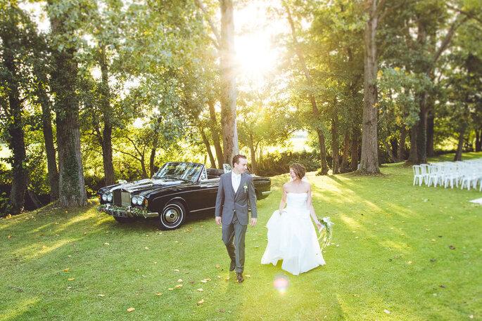 Les mariés sortent de leur voiture et arrivent sur leur lieu de réception, sourires aux lèvres