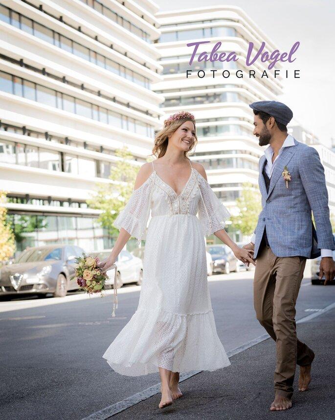 Das Brautpaar beim Shooting und schlendern vor einer Stadtkulisse, dazu der Schriftzug: Tabea Vogel Fotografie.