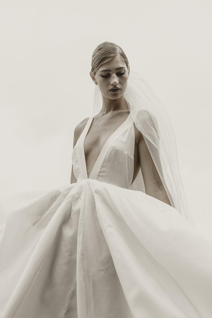 Une mariée avec une robe au décolleté très plongeant et un voile