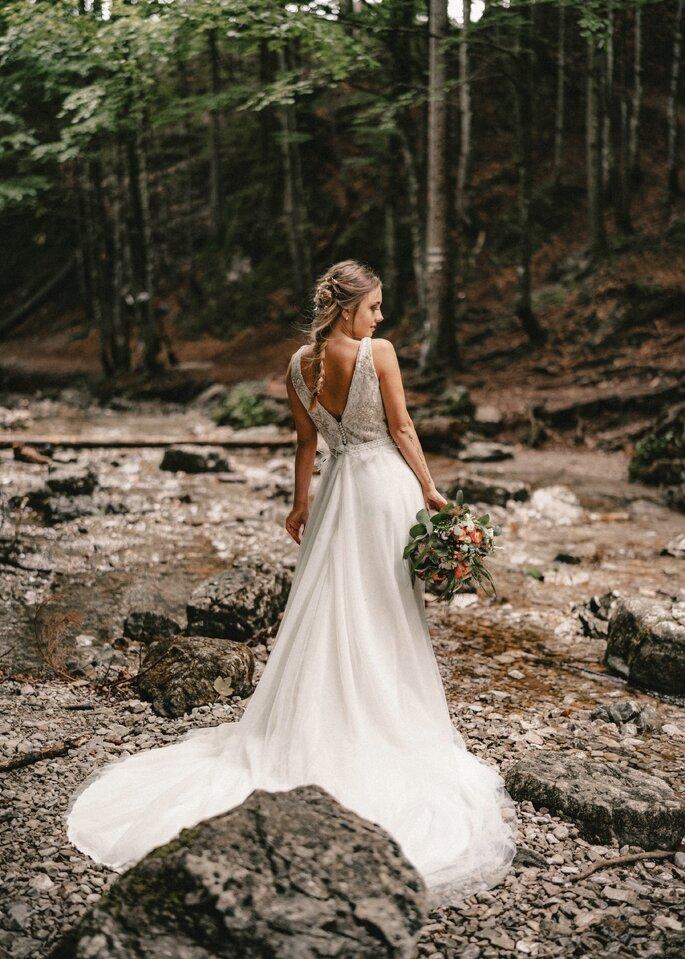Brautkleid vor Wald. Steht mit Rücken zur Kamera und hält Brautstrauß in der rechten Hand.