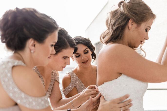 Getting Ready. Brautjungfern helfen der Braut beim anziehen des Brautkleides
