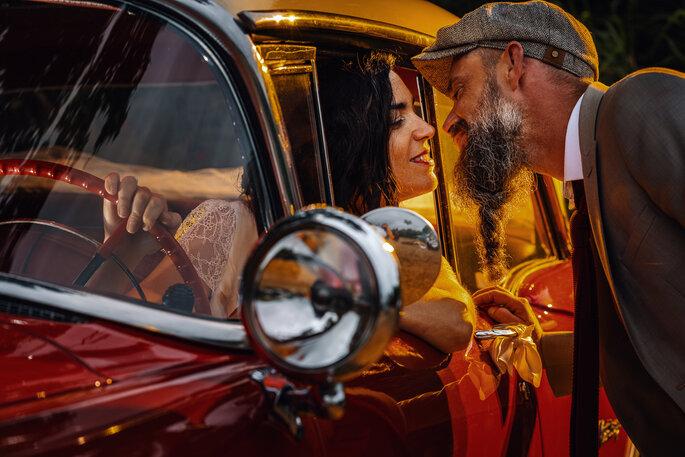 Deux mariés s'embrassent dans une voiture