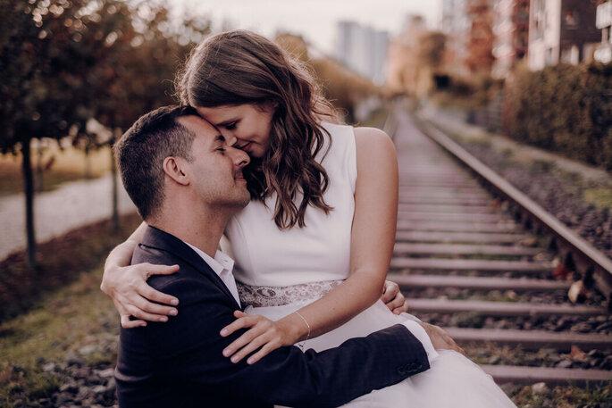 Ein Brautpaar sitzt auf Gleisen und schaut sich tief in die Augen.