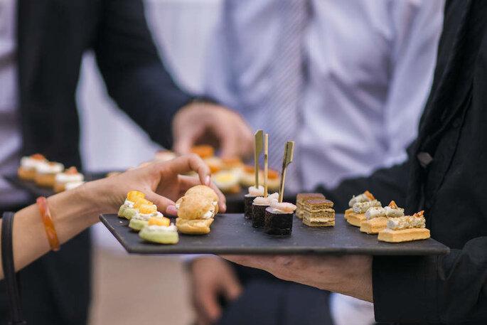 Des amuses-bouches salés disposés sur un plateau et servis aux invités lors d'un mariage