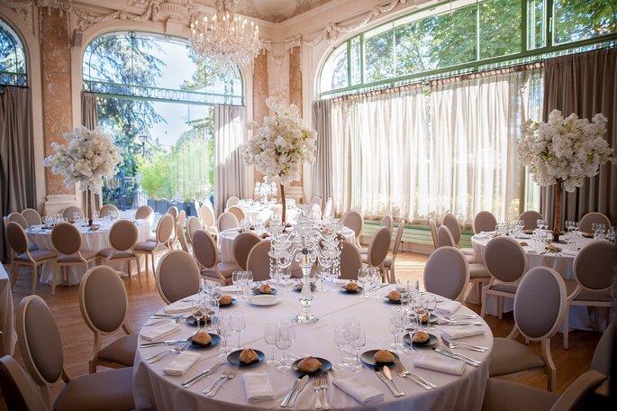 Salle de réception de mariage avec de superbes lustres à pampilles et de grandes baies vitrées style Belle Époque