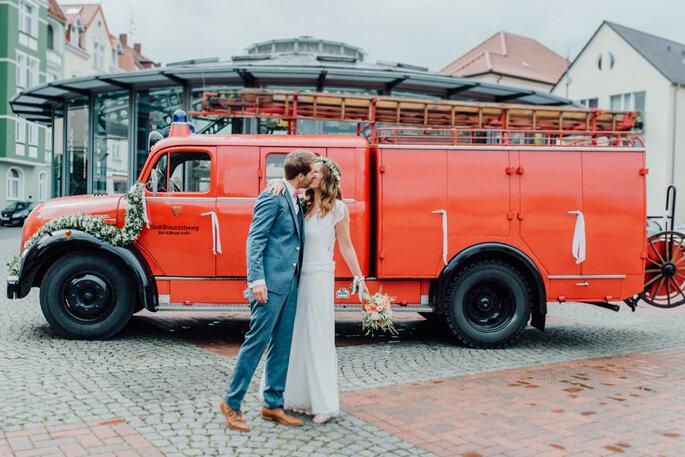besonderes Hochzeitsauto mit küssendem Brautpaar