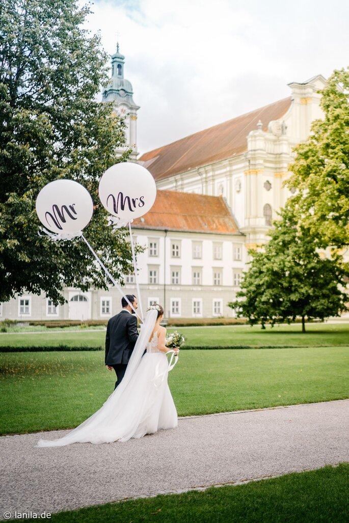 Brautpaar mit Mr & Mrs Luftballons auf einer Wiese vor einer Kirche