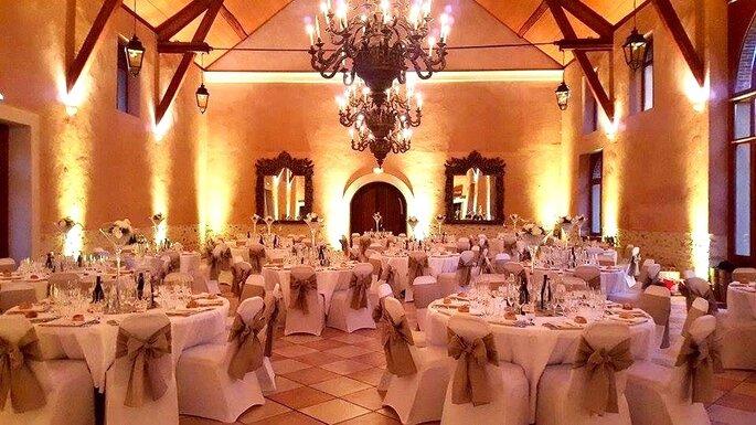 La salle de banquet du mariage ornée de grands candélabres, au moment du dessert
