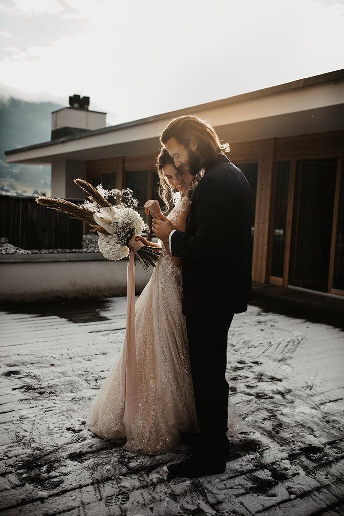 Das Brautpaar liegt sich in den Armen.