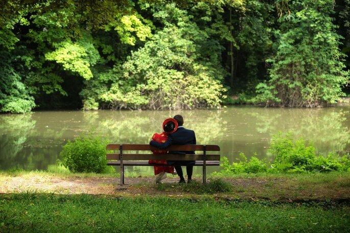 Une séance d'engagement mise en scène par un photographe de mariage, en pleine nature, deux futurs mariés sont enlacés sur un banc, de dos, face à un lac