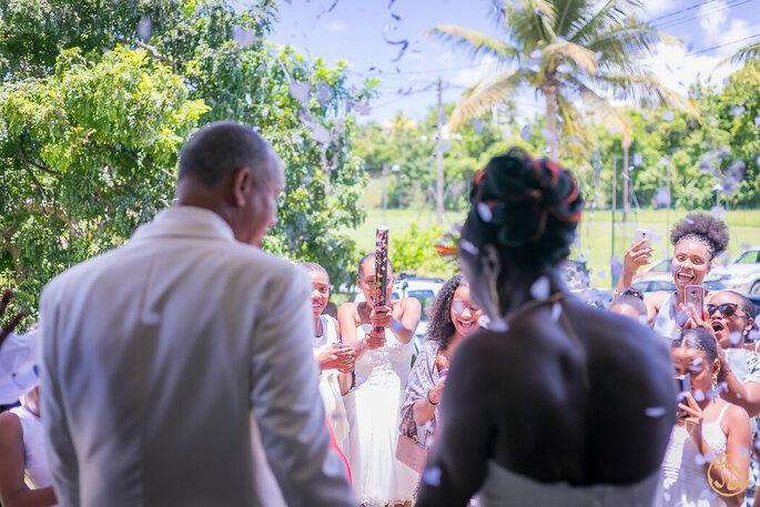 Deux mariés photographiés de dos avec leurs invités qui les prennent en photos