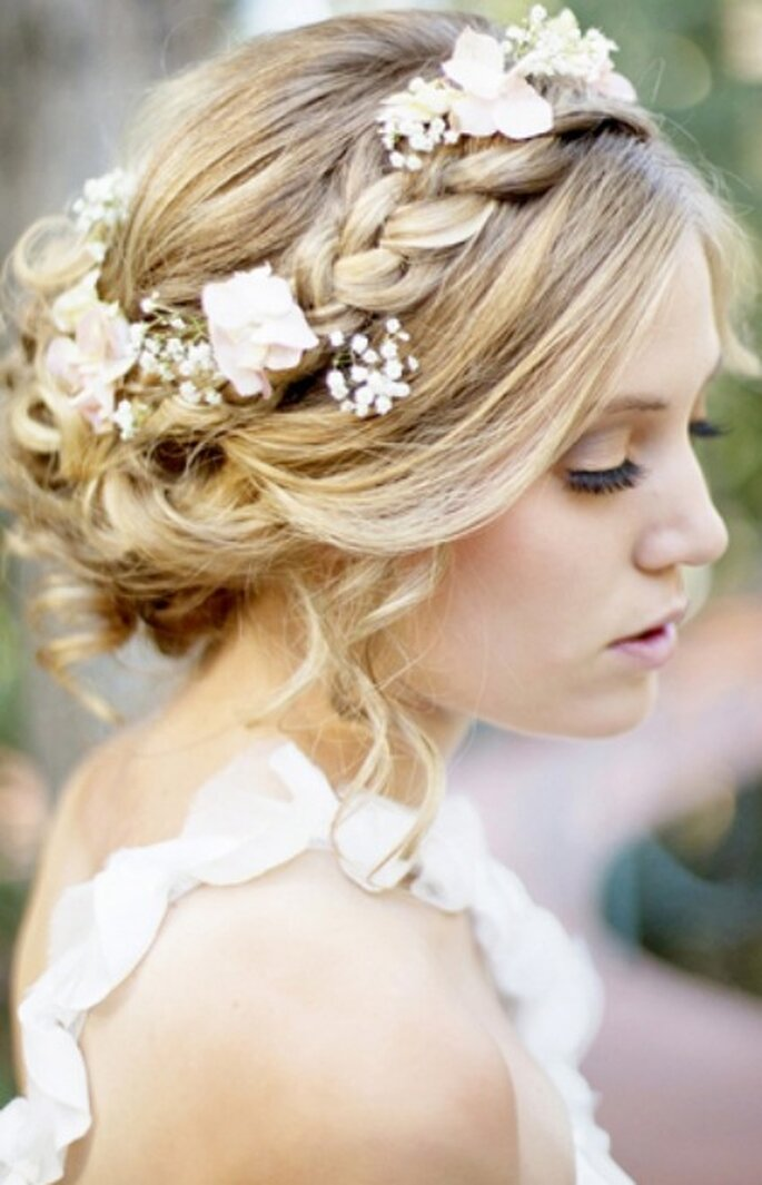 Peinado de novia con corona trenzada y flores. Foto: Trendy Wedding