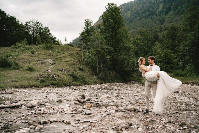 Bräutigam trägt seine Braut auf Händen. Im Hintergrund grüne Bäume.