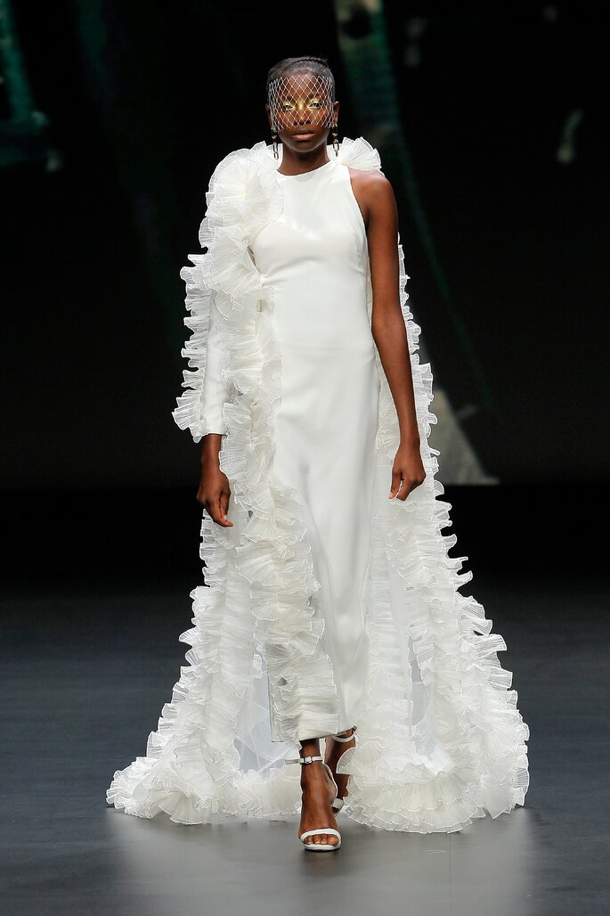 Colección Touch de Yolan Cris - Vestido de novia blanco roto de crepe con la silueta larga en forma de tubo. Manga asimétrica con cascadas de volantes de organza de seda plisada. Capa plisada