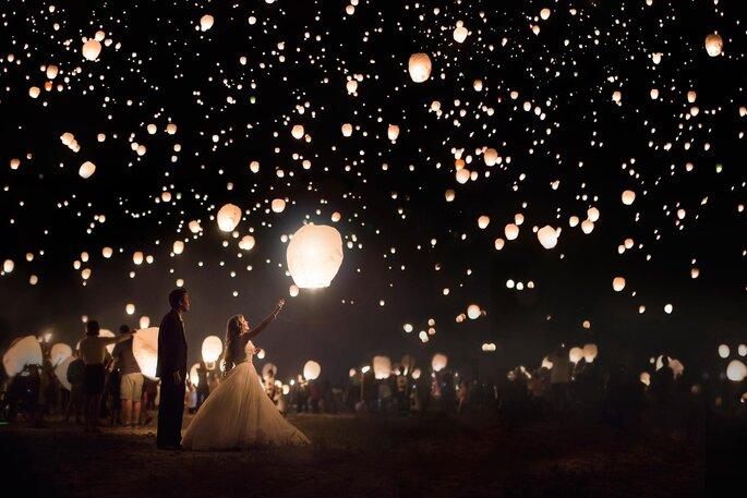 noivos e convidados lanternas chinesas no céu noite escura