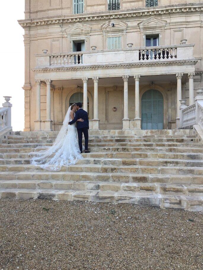 La façade château soit d'un lieu de réception pour votre mariage - deux mariés s'embrassent sur le perron