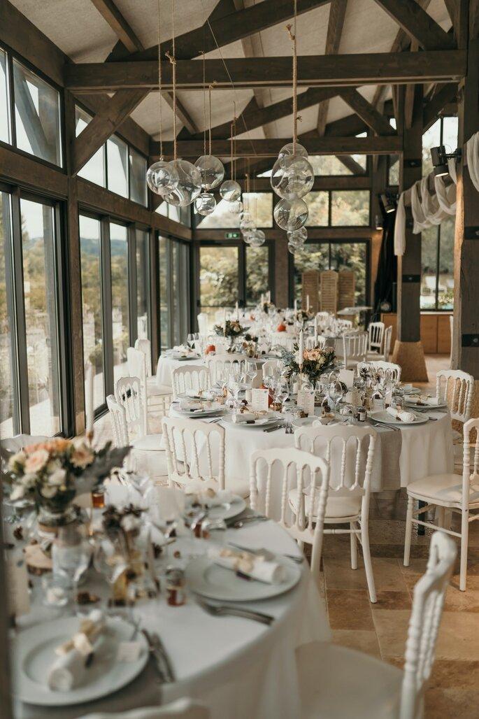 Les tables sont dressées pour le diner de réception avec une décoration végétale et raffinée