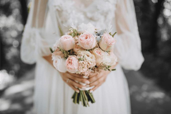 Une mariée tenant son bouquet de fleurs à la main.