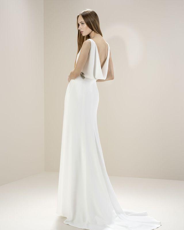 Утонченное креповое платье, с элегантной спиной в виде ниспадающих драпировок. Корсет задекорирован камнями.
