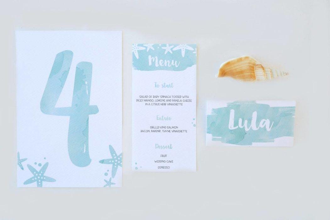 Dettagli (segnaposto, segnatavolo e menu) di un matrimonio on the beach