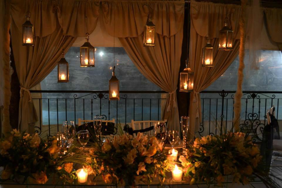 Enmarcación de mesa de honor a la luz de faroles y mesa de cristal. El romanticismo en su mayor esplendor.
