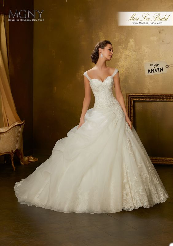 Style ANVIN Oribel  Crystal beaded, embroidered lace appliqués with asymmetrically draped organza flounce on tulle ball gown trimmed with wide hemlace  Detachable shoulder straps