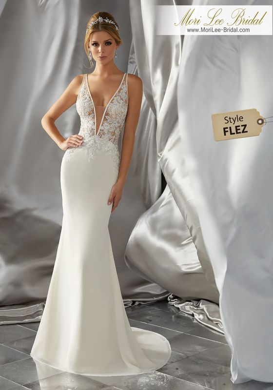 Style FLEZ Malin Wedding Dress  Perfect for the Daring Bride, This Sultry Wedding Dress Features a Soft Chiffon Skirt and Crystal Beaded, Embroidered Bodice with Satin Trimmed Sheer Plunging V-Neckline. Matching Satin Bodice Lining Included. An Open Back with Covered Button Detail Completes the Look. Colors Available: White, Ivory, Ivory/Light Gold.