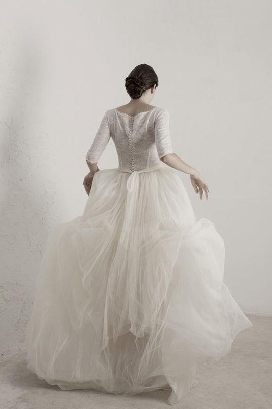 Matilda Vestido de tul de seda con encaje y forro de seda en la parte superior y con manga tres cuartos y con abotonadura en la parte posterior. La falda tiene varias capas de organza para dar un mayor volumen.