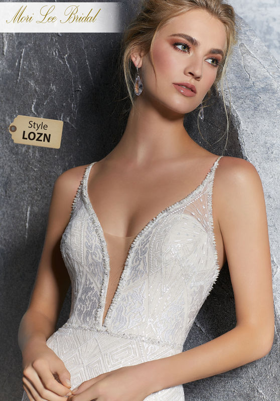 Style LOZN  Kendra Wedding Dress  Deco Beaded Sheath with Metallic Embroidery on Net. The Plunging Illusion Neckline is Trimmed in Beading and Open Back is Accented with Braided Shoulder Straps. A Zipper Back Closure Trimmed in Buttons Completes the Look. Available in Three lengths: 55″, 58″, 61″. Colors Available: White, Ivory, Ivory/Light Nude