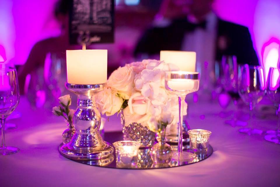 Centro con bases de plata vieja. Pedestales de plata con espejo de base. Velas que dan el toque cálido a la composición. http://lafloreria.net