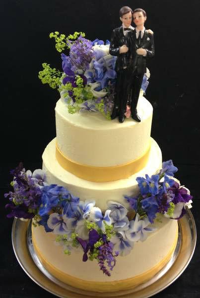 Dreistöckige Hochzeitstorte mit echtem Blumentrauß oben in die Torte eingesetzt.   Mit weiteren Blumen auf der mittleren Etage verziert.