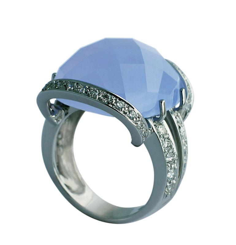 Un diseño con aire años 40. Es de oro blanco con calcedonia azul tallada en damero y cuajado de diamantes. Diseño exclusivo de Victoria de la Calva.