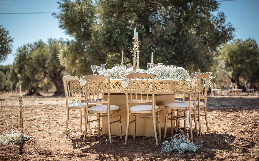 Tavolo St. Regis, Sedia Parigina in legno color oro, piatti in vetro con filo oro, bicchieri in vetro con filo oro, posate vintage oro, monocandela veneziono.